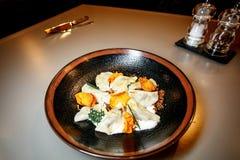 Klimpar hemlagad ravioli i en platta på svart bakgrund arkivfoton