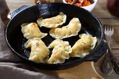 Klimpar med potatisar i en stekpanna royaltyfria foton