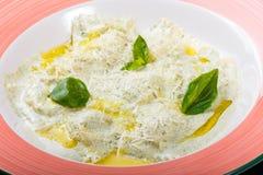 Klimpar med potatisar som garneras med parmesan, ostsås, olja och basilika på plattan på svart träbakgrund arkivbilder