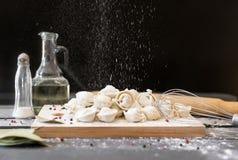 Klimpar på brädet, mjöl häller svrehuen, Corolla, oljaflaska, saltar shaker, kryddor, mörk bakgrund royaltyfri foto