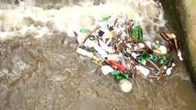 Klingerytów inny i butelki bałaganią obracać dalej poziom wody Kręcenie brudna woda nad jaz na małej rzece z błotnistą wodą zbiory
