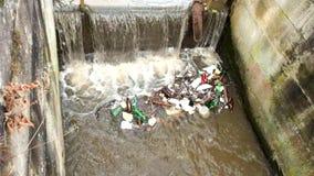 Klingerytów inny i butelki bałaganią obracać dalej poziom wody Kręcenie brudna woda nad jaz na małej rzece z błotnistą wodą zdjęcie wideo