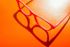 Klingerytów różowi eyeglasses z cieniem na pomarańczowym pogodnym tle Kolorowy poj?cie fotografia stock