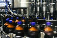 Klingeryt butelkuje poruszającego na konwejeru pasku Zdjęcie Stock