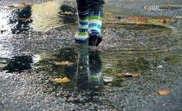 Klingeryt inicjuje bieg przez kałuży w jesieni obraz royalty free