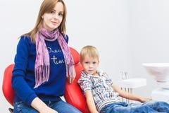 klinika stomatologicznej Przyjęcie, egzamin pacjent Ząb opieka Chłopiec z jego matką siedzi w stomatologicznym obraz stock