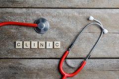 Klinika teksta słowo robić z drewnianymi blokami i Czerwonym sercem, stetoskop Fotografia Stock