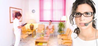 Klinikempfangsdame, die im Kopfhörer benennt Stockfoto