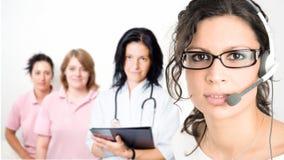 Klinikempfangsdame im Kopfhörer Stockfotos