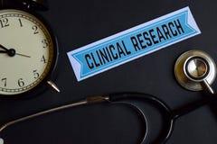 Klinische Forschung auf dem Druckpapier mit Gesundheitswesen-Konzept-Inspiration Wecker, schwarzes Stethoskop stockfotos