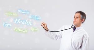Klinisk doktor som pekar till hälso- och konditionsamlingen av wor Arkivbild