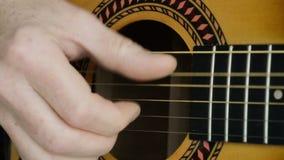 Klinka för akustisk gitarr Närbild av en hand som klinkar den klassiska gitarren arkivfilmer