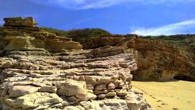 Klip en rotsvormingen op Nazare-strand in Portugal Close-up stock videobeelden