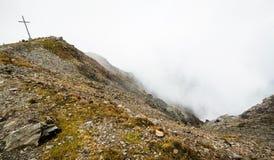 Klip met kruis boven wolken in bergen van Oostenrijk Royalty-vrije Stock Foto's