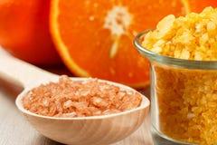 Klipp apelsinen, träsked med den bruna salta och glass bunken för havet med Royaltyfri Bild