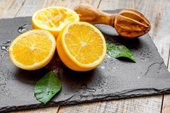 Klipp apelsiner i halva och juiceren på träbakgrund Royaltyfri Bild