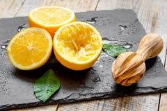 Klipp apelsiner i halva och juiceren på träbakgrund Royaltyfri Fotografi