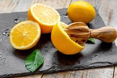 Klipp apelsiner i halva och juiceren på träbakgrund Royaltyfri Foto