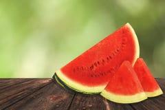 Klipp den nya saftiga vattenmelon på ett träbrun skrivbord eller tabell Suddig grön bakgrund av en parkera fotografering för bildbyråer