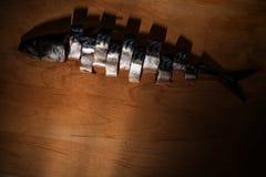 Klipp fisken i stycken på träbräde royaltyfri fotografi