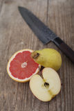 Klipp frukt på träyttersida med kniven Royaltyfria Bilder