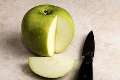 Klipp gröna Apple med kniven på räknareöverkant Arkivbilder