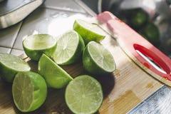 Klipp gröna limefrukter på en Wood skärbräda arkivfoton
