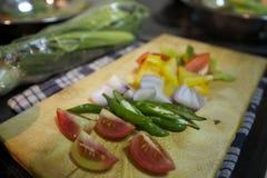 Klipp grönsaken med det choping brädet Royaltyfri Fotografi