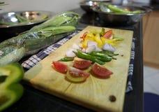 Klipp grönsaken med det choping brädet Arkivbilder