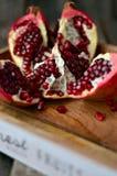 Klipp granatäpplet på trätabellen, Arkivfoton