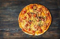 Klipp in i skivor läckra ny pizza med tomater och oliv på en mörk bakgrund Top beskådar Pizza på den wood tabellen Royaltyfri Bild