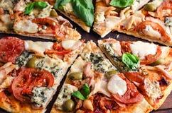 Klipp in i skivor läckra pizza på trätabellen arkivbild