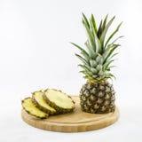 Klipp och skivade ananas på träbräde Arkivbild
