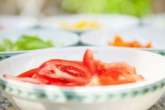 Klipp rå tomater i en bunke som är förberedd för att laga mat bbq, rå ingrediens Fotografering för Bildbyråer