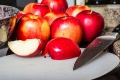 Klipp röda äpplen med kniven Arkivbild