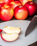 Klipp röda äpplen med kniven Arkivfoton
