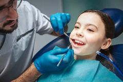 Klipp sikten av den manliga tandläkaren som gör upp kontrollen av flickmunnen Han använder tand- hjälpmedel Flickan sitter i stol royaltyfri fotografi