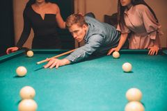 Klipp sikten av den unga mannen som ser koncentrerad Honom som siktar in i billiardboll Två slanka modeller står bak honom royaltyfri bild