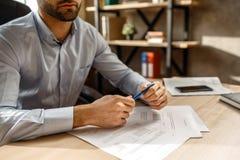 Klipp sikten av den unga stiliga affärsmannen i hans eget kontor Han rymmer pennan i händer Dokument på tabellen Sätta häftet fotografering för bildbyråer