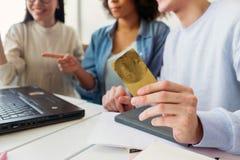 Klipp sikten av en grabb som rymmer en kreditkort i hans händer, medan han ser bärbara datorn med flickor tillsammans Arkivbild