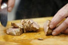 Klipp varmt stekt kött på en skärbräda arkivfoton