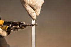 Klippa av metallstången med kraftig industriell hand-fungeringssax med händer arkivbild