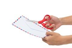 Klippa en bokstav som öppnar ett kuvert med isolerad sax royaltyfria foton