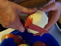 Klippa ett äpple med kniven Royaltyfria Foton