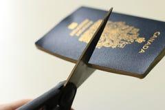 Klippa ett kanadensiskt pass Begrepp av att avs?ga sig medborgarskap eller att l?mna landet Dissastisfaction med Kanada royaltyfria bilder