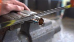 Klippa ett metallrör med en bågfil stock video
