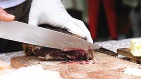 Klippa ett stycke av torr skinka med kniven stock video