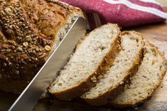 Klippa Multigrain bröd in i skivor på skärbräda Royaltyfri Bild