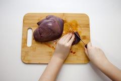 Klippa ny grisköttlever En kvinna klipper levern på en skärbräda royaltyfri bild