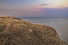 Klippa- och havssoluppgång för torrt gräs Arkivbilder